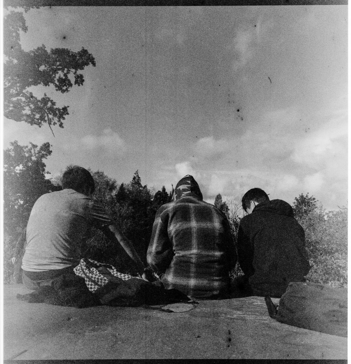 Three young men sit on a concrete platform, their backs to the camera.