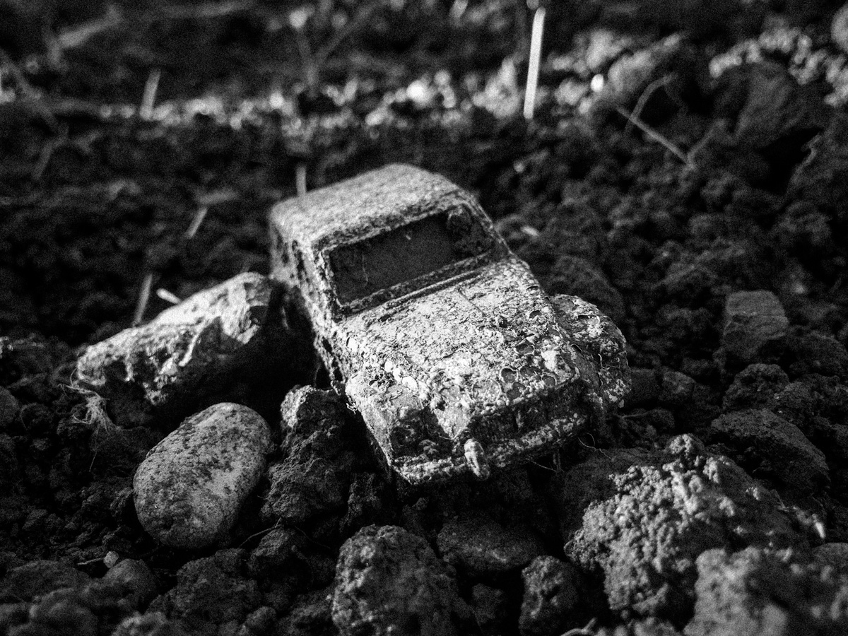A toy car (a 2CV I think) lies rotting in garden soil.