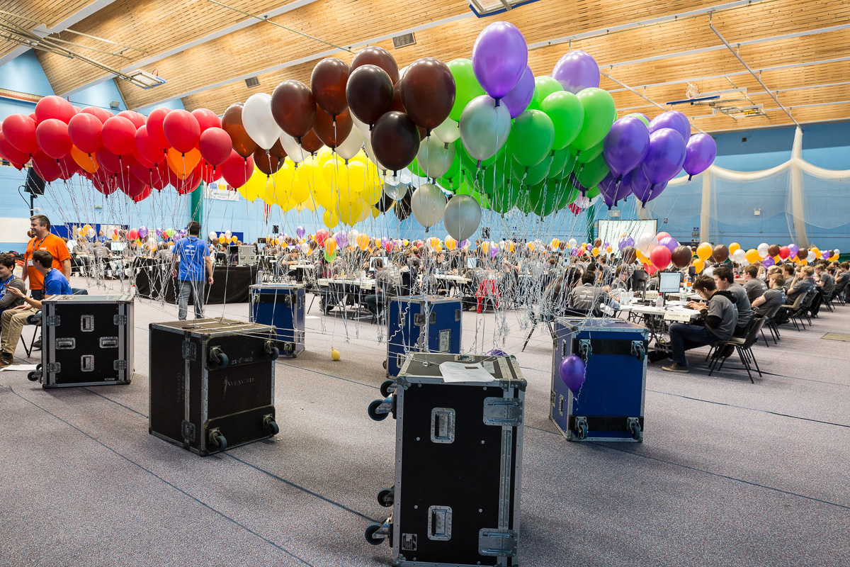 Different coloured balloons are tethered to roadie boxes as teams work in the background.