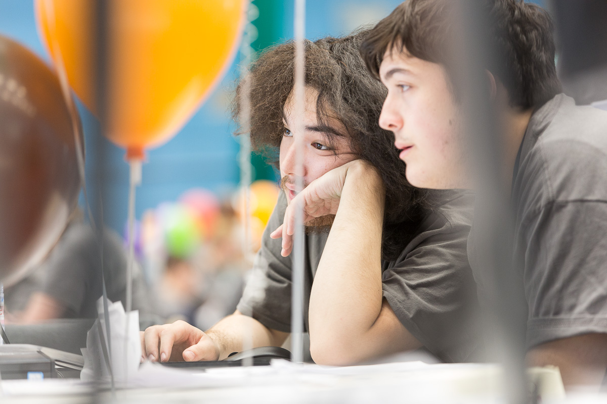 Two male students, seen side-on through balloon strings as they work at their computer.