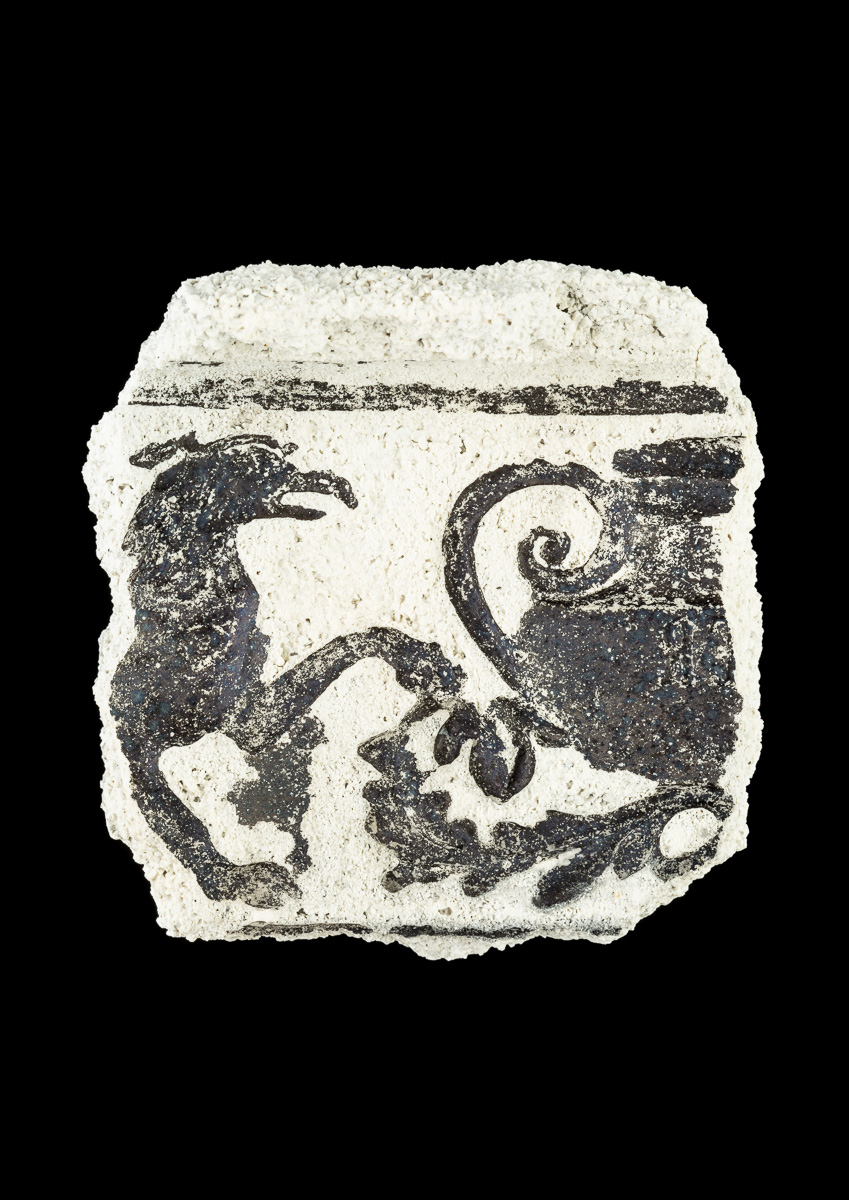 Impression of mythical creature and pot design in ceramic fragment.