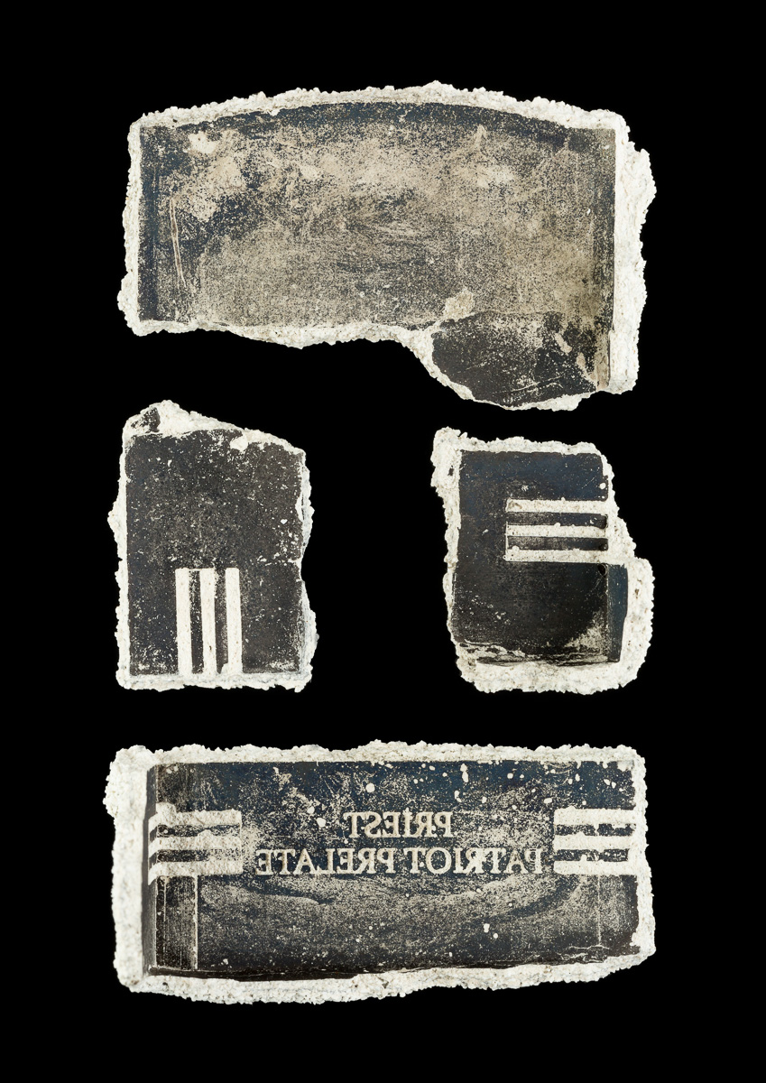Fragments of ceramic casing from the casting of a bronze base arranged in a rectangle.