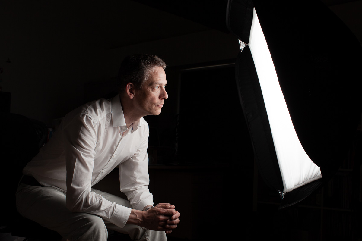 Photographer Tim Gander sits looking into a studio flash softbox which lights his face in an otherwise dark room.