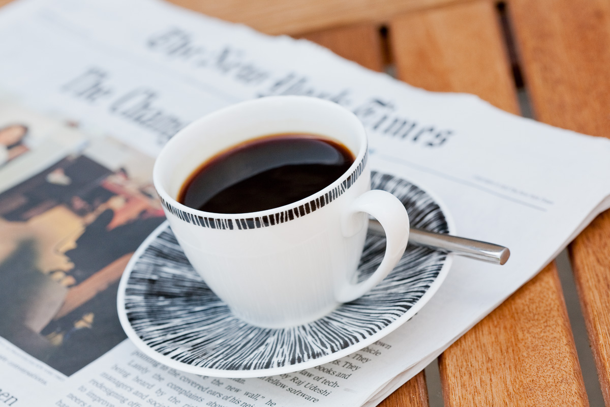 A cup of espresso sits on an out of focus copy of the New York Times.