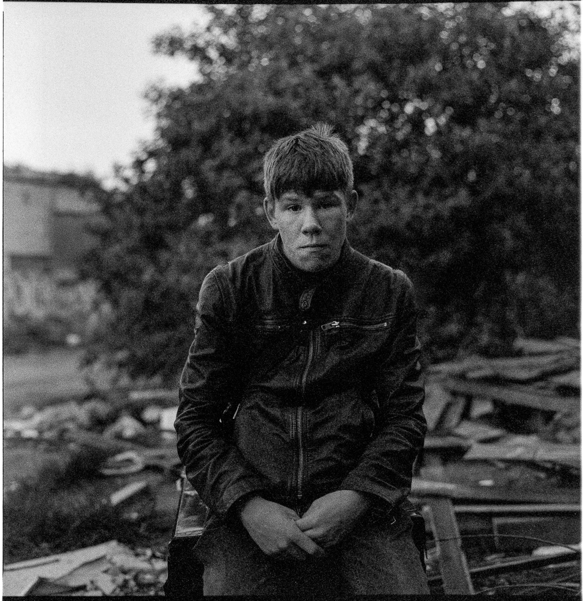 Grainy black and white portrait of a male youth seated on a discarded container, looking to camera. He looks very serious.