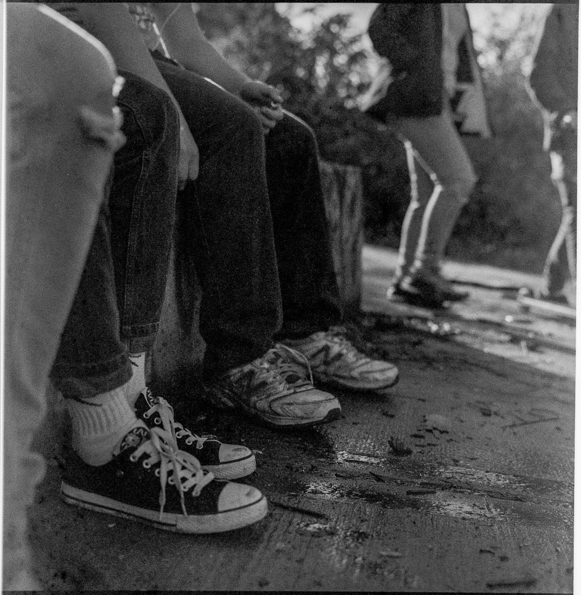 Black and white view of the feet and legs of youths seated while others walk past in the background.