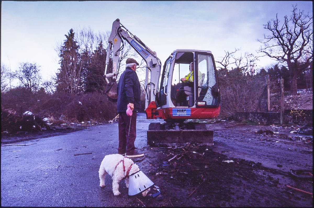 Colour photo of a dog walker chatting to a digger operator in charge of clearing up the site. The dog is wearing a neck cone.