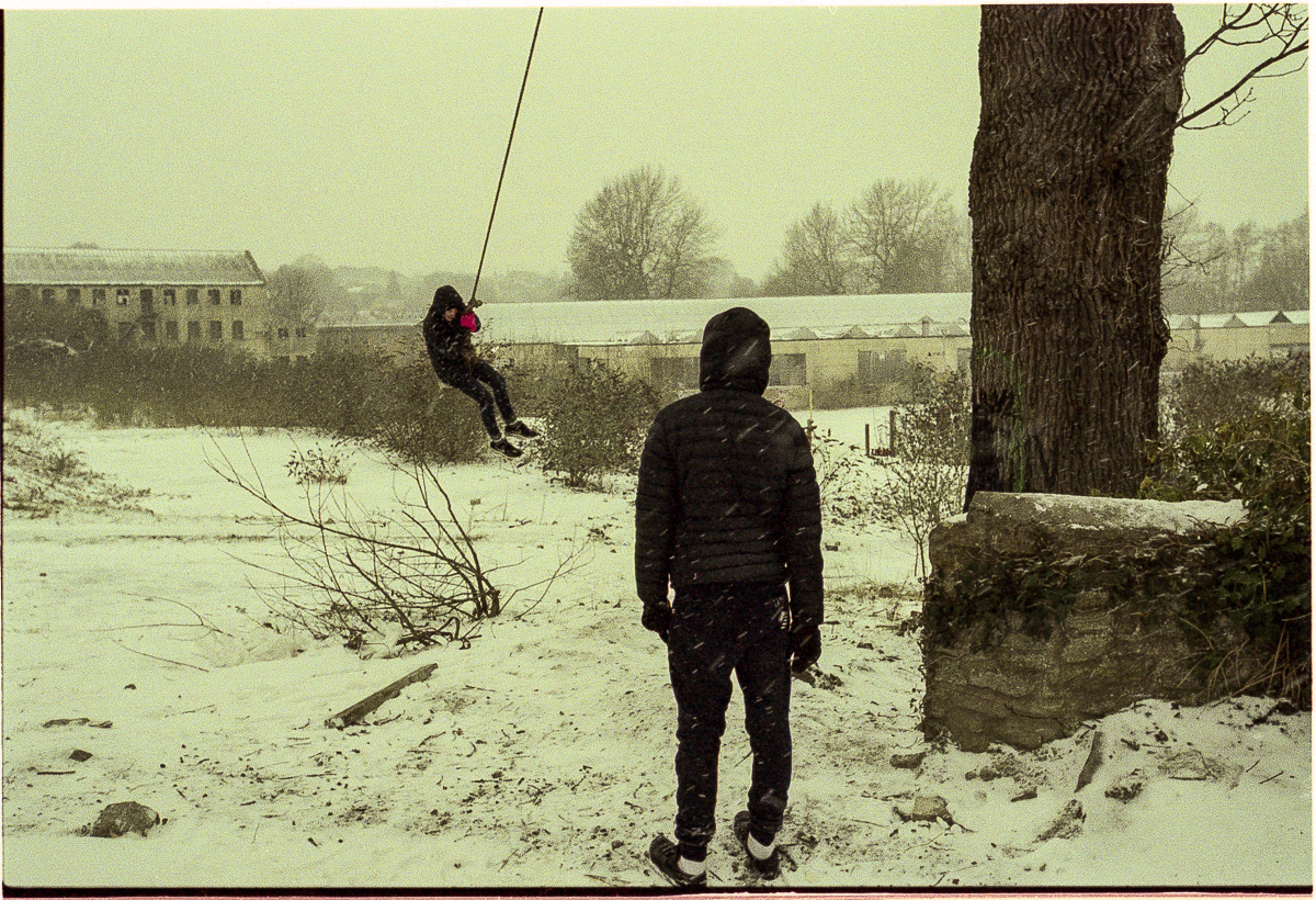 Colour photo of two boys playing in snow. One stands, back to camera, while the other swings away on a rope swing suspended from a tree.