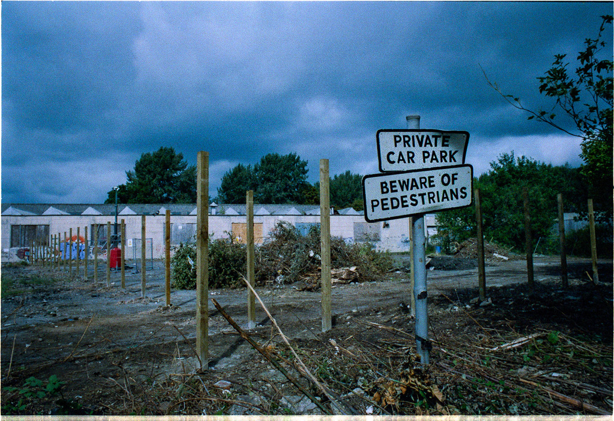"""In the foreground a battered sign reads """"Private care park. Beware of Pedestrians"""". Bare wooden upright posts lead away to the background to low, old industrial sheds and a brooding sky."""