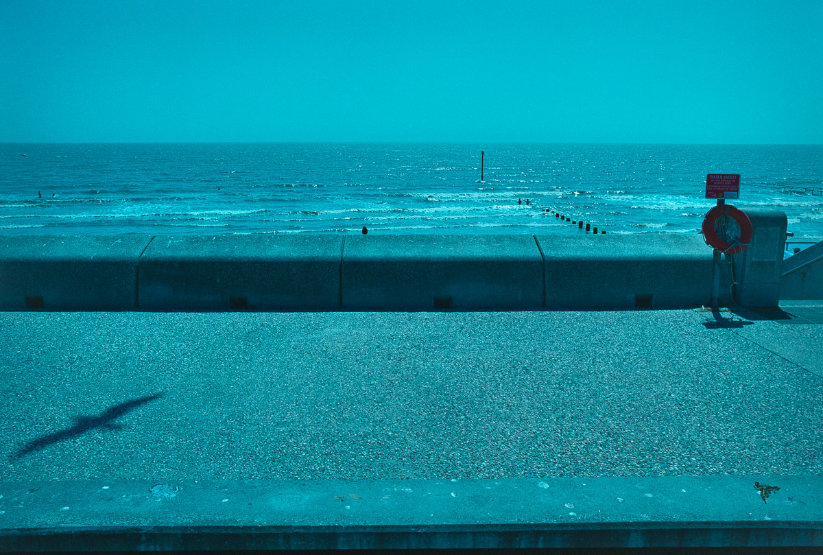 Landscape view looking out to sea across the width of the concrete promenade at Dymchurch in Kent.