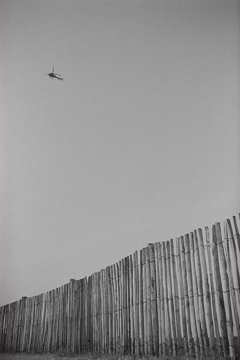 A wooden stick fence dominates the foreground as a helicopter, very small in the frame, crosses the clear sky above.