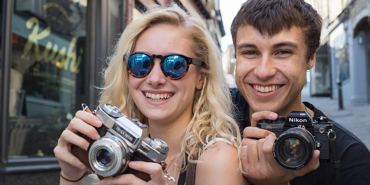 A young blonde female and her brunette boyfriend holding cameras and smiling at the camera.