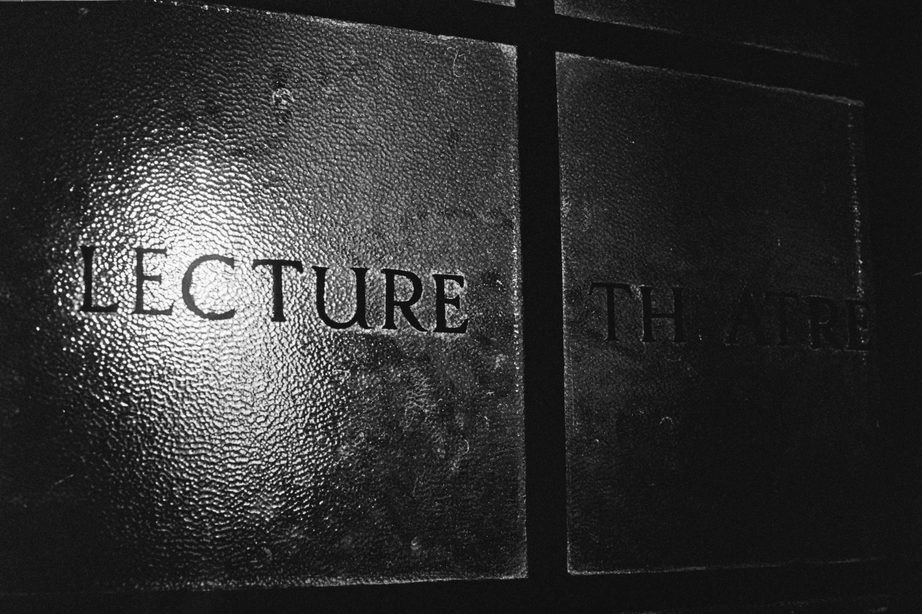 "Black and white photo of the word ""Lecture"" written on obscuring glass, illuminated from behind by an unseen light bulb."