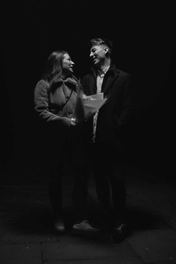 black and white photo of a young male and female couple standing looking at each other. She is holding flowers wrapped in paper.