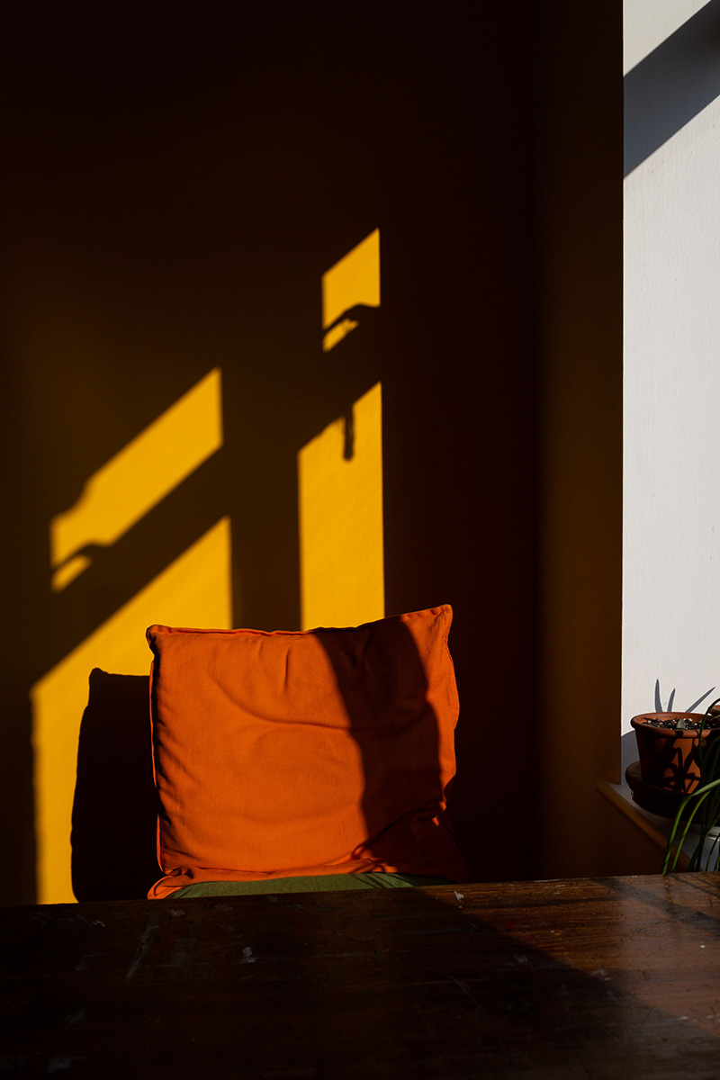 Window light casts the shadow of the window frame onto a bright yellow wall. A chair in front of the wall sports a bright, burnt orange cushion.