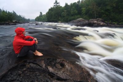 Tim Irvin sitting beside waterfall on Coulonge River, Quebec