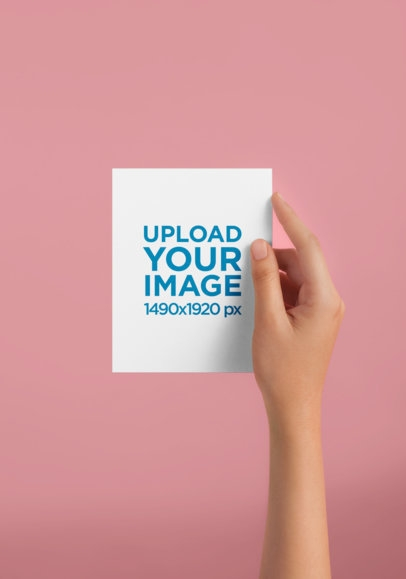placeit womans hand holding a vertical postcard mockup against a
