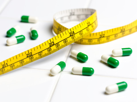 weight loss pills and tape measure