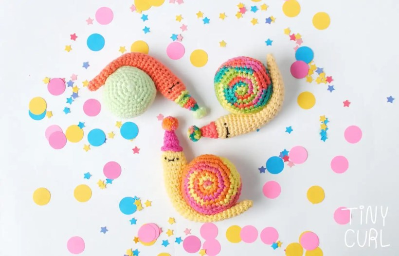 Three Party Snail amigurumi dolls doing the spiral dance. These were made with the free amigurumi pattern from Tiny Curl.