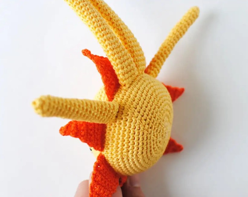 Close up shot of the bottom of the amigurumi Sun in order to show how the arms and legs are attached.