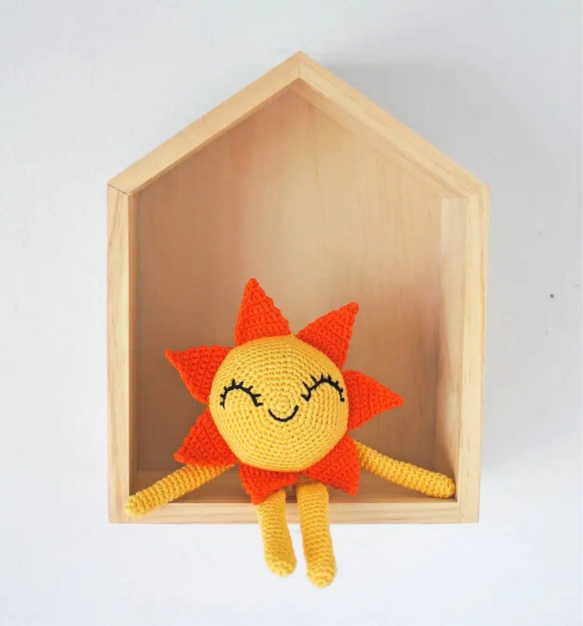 Happy little amigurumi Sun sitting in its house with a smile embroidered on its face.