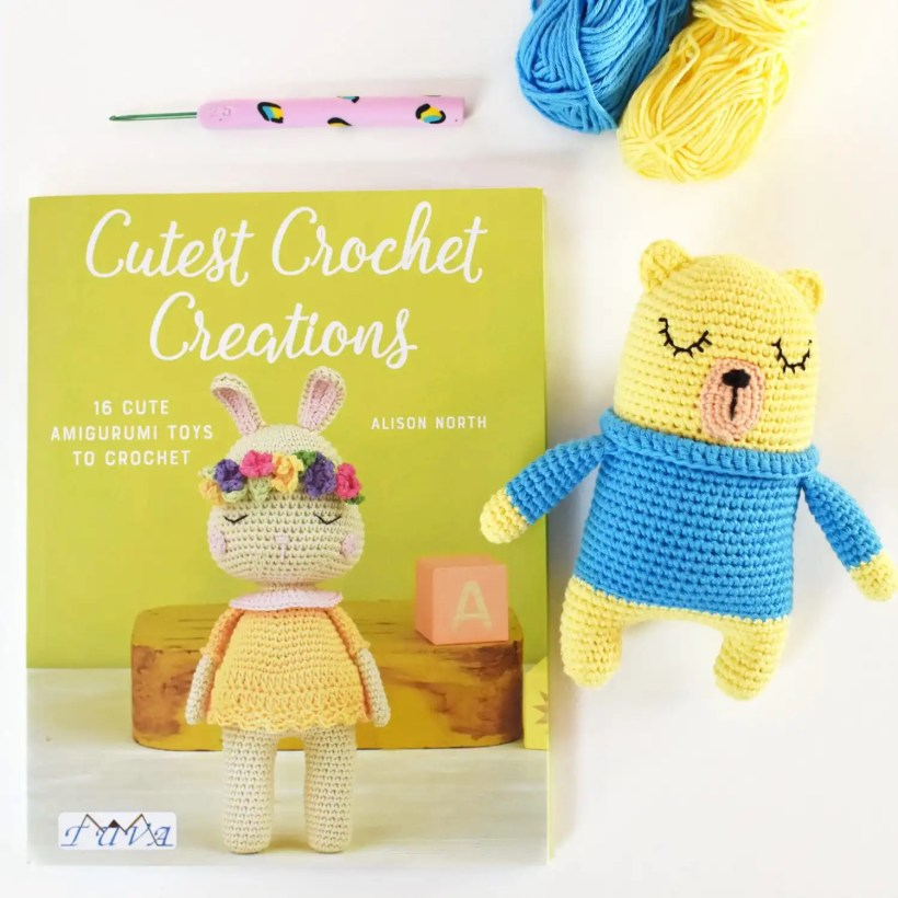 Image of the Cutest Crochet Creations Book by Alison North. An amigurumi crochet bear that was made from the book. A crochet hook and two balls of yarn.