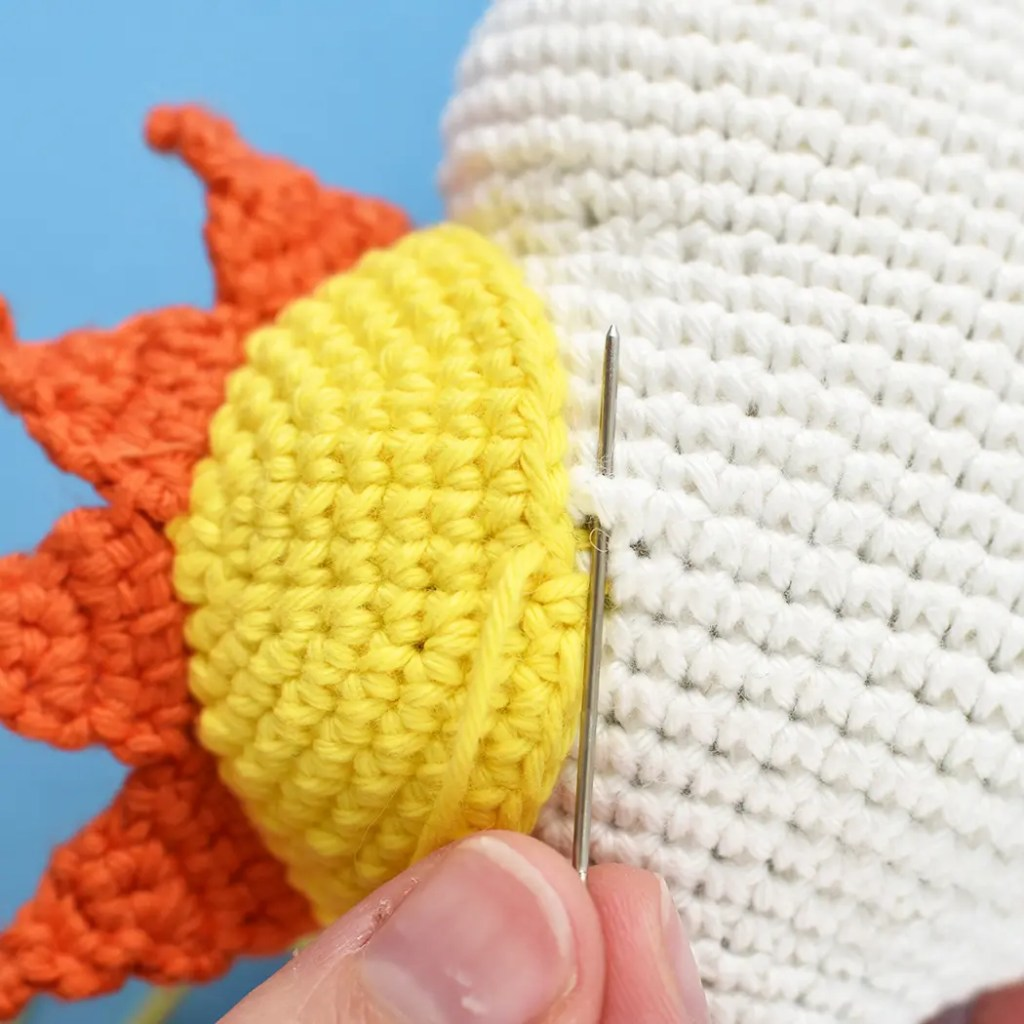 Showing how to attach and sew sun hat to top of crochet cloud using tapestry needle.