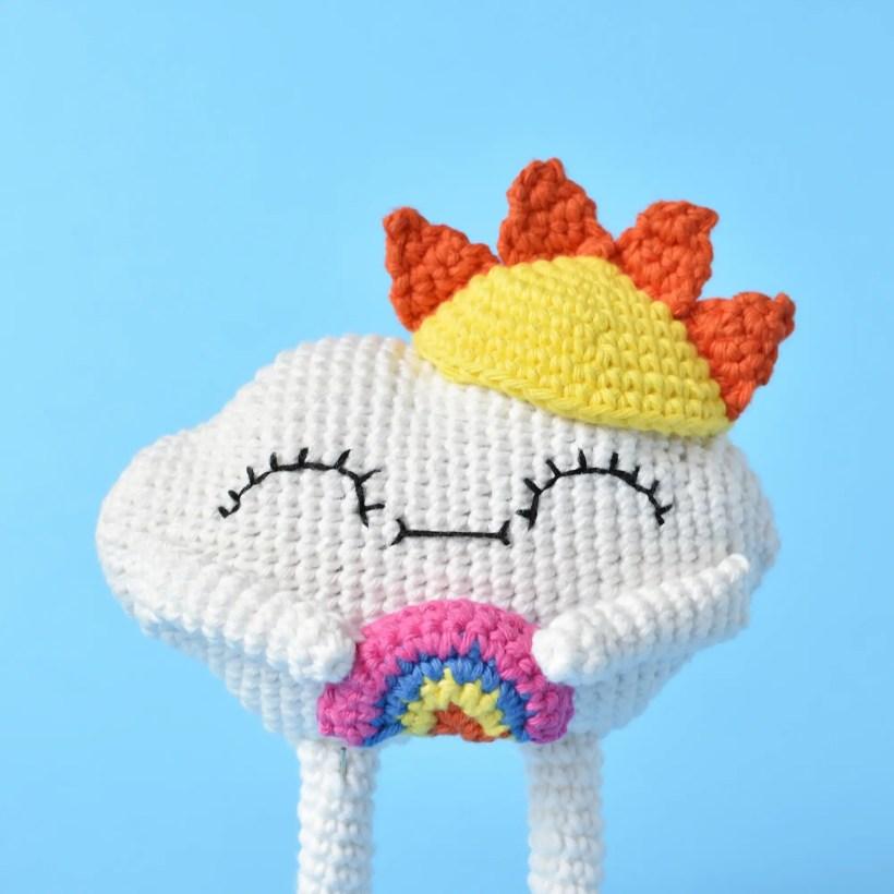 Amigurumi cloud crochet doll with a sun hat holding a rainbow
