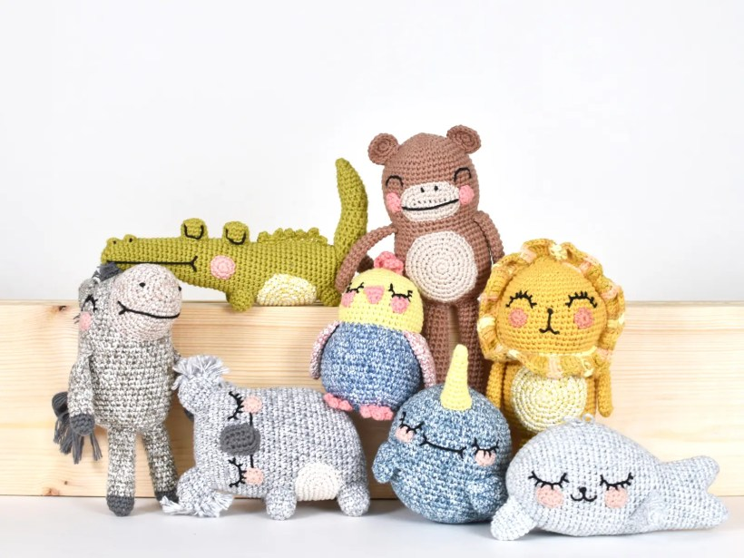 A group of crocheted animals sit in front of a wooden plank on a white backdrop. The animals include a crochet alligator, amigurumi monkey, crochet donkey, amigurumi koala, amigurumi bird, crochet lion, amigurumi narwhal, and crochet seal.