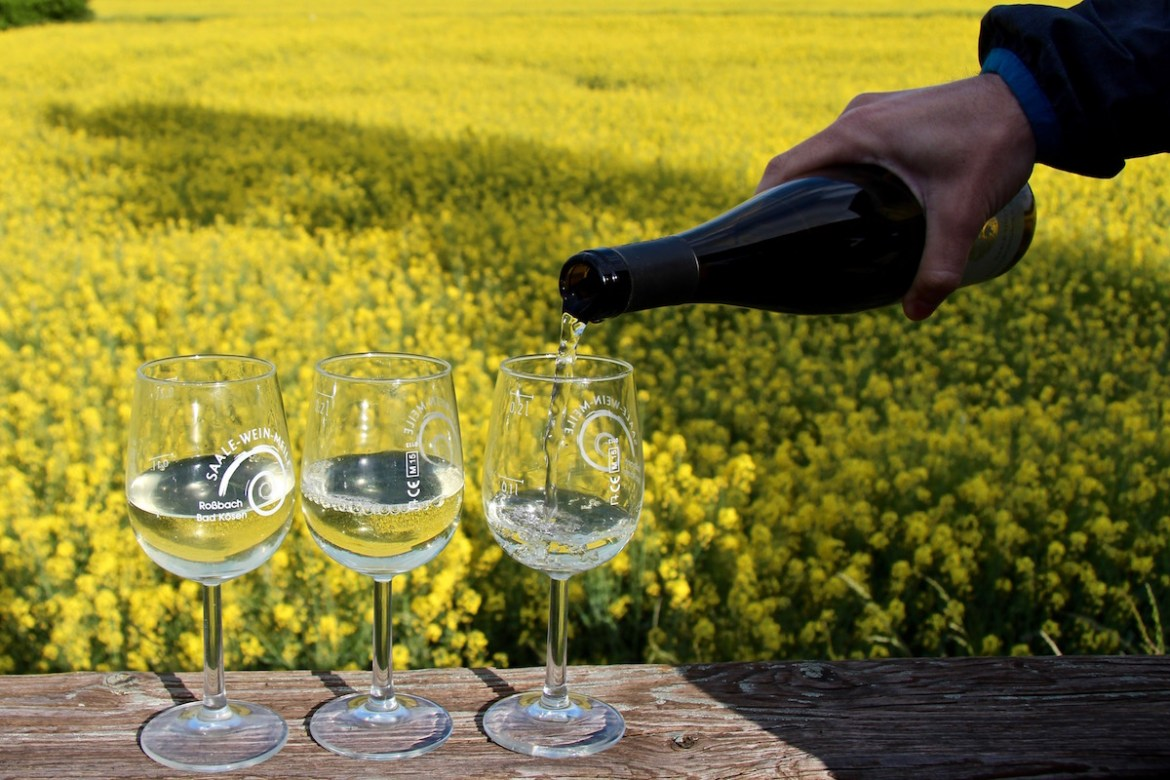 Refilling wine against rapeseed flower fields