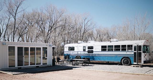 @trebventure skoolie parked by their container home.