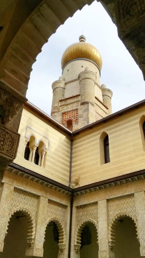 Vista dal cortile con la fontana dei leoni sulla cupola dorata della Rocchetta Mattei