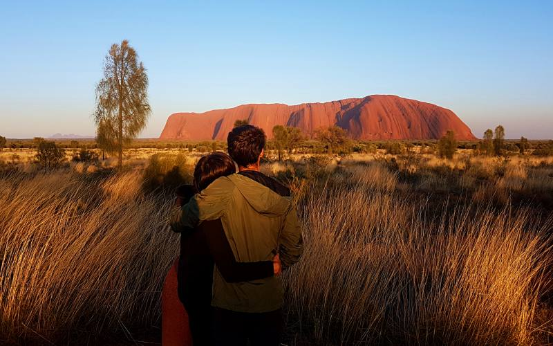 Foto di coppia davanti Uluru (Ayers Rock) all'alba