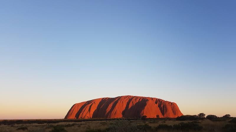 Uluru al tramonto di un colore arancione acceso visto dal punto panoramico Car Sunset Viewing