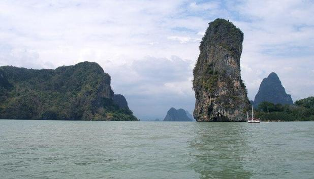 A couple relaxes on a beach in Phang Nga Bay on one of the best islands to go for a honeymoon in Thailand