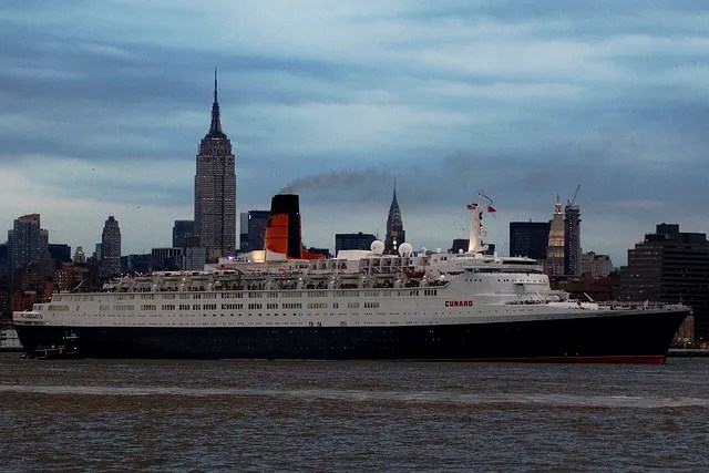 Cunard Queen Elizabeth 2 New York with the Empire State Building and the Chrysler Building in the background.