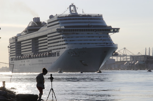 MSC Divina loomed large against one of the reporters on the bank