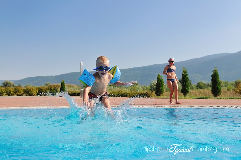 happy kids have fun on outdoor swimming pool at beautiful aquapark