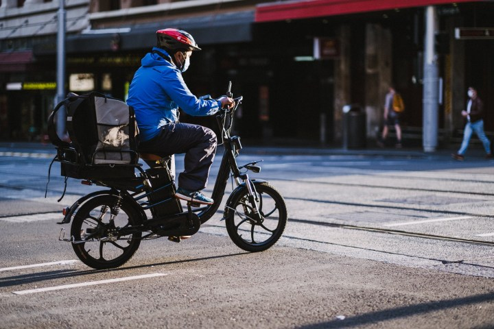 man in blue jacket riding motorcycle on road