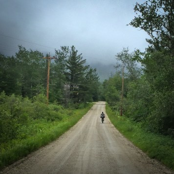Jonathan pedaling through light rain along Silver Lake Road. This photo does no justice to the sense of scale and openness one feels out here.