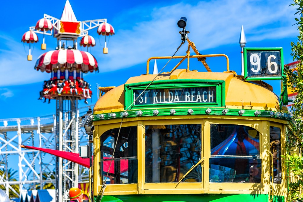Vintage Melbourne W-Class Tram Images in St Kilda with fun fair rides in the background