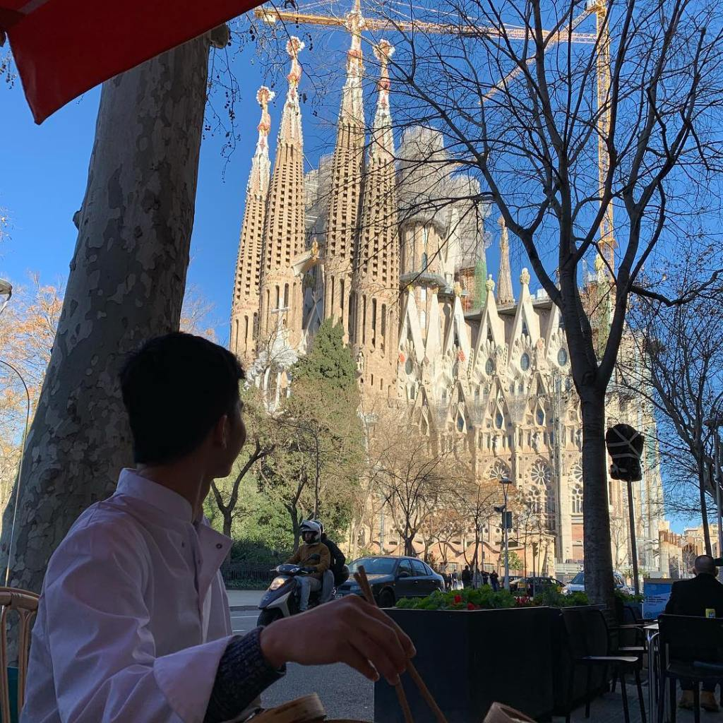 A man uses chopsticks to eat dim sum while looking at the Sagrada Familia from an outdoor seating area.