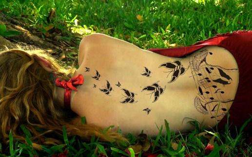 Chica tumbada en la hierba de espaldas a la cámara con la espalda al descubierto y toda ella tatuada