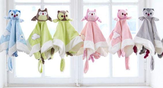 Foto con seis doudou (muñecos de bebés) colgados del techo. En el fondo una ventana blanca.