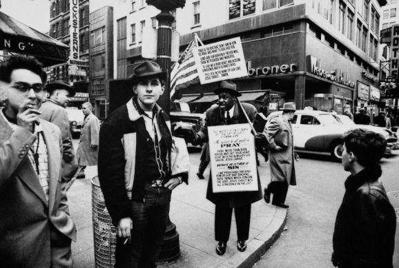 Foto urbana en blanco y negro donde figuran varias personas por la calle andando y algunas de ellas mirando a la cámara