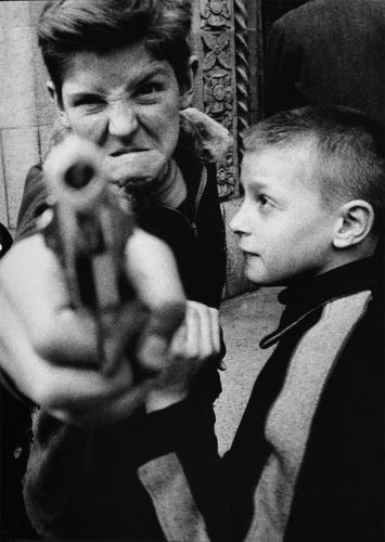 Foto en blanco y negro de dos niños, uno de ellos apunta con una pistola directamente a la cámara.