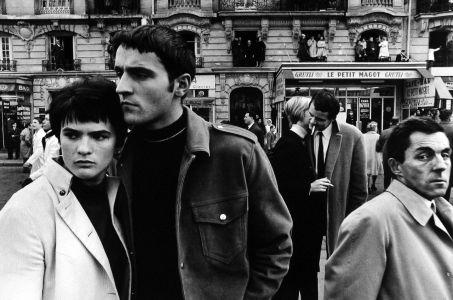 Foto en blanco y negro en una ciudad francesa donde aparecen parejas de personas mientras van por la calle