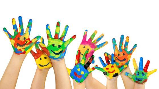 Imagen con manos de niños pintadas con muchos colores, recortada sobre fondo blanco.