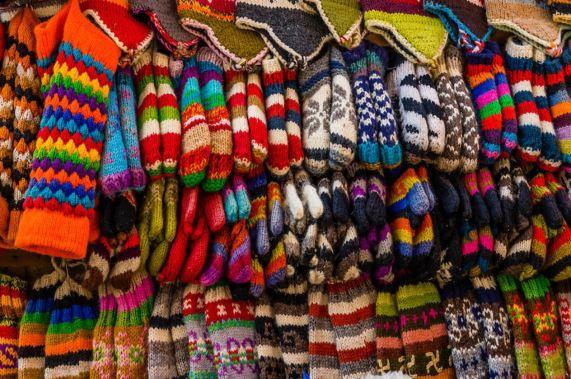 Imagen con un montón de ropa de lana colgada como una tienda de mercado