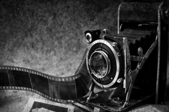 Imagen en blanco y negro de una cámara reflex antigua sobre un fondo gris.